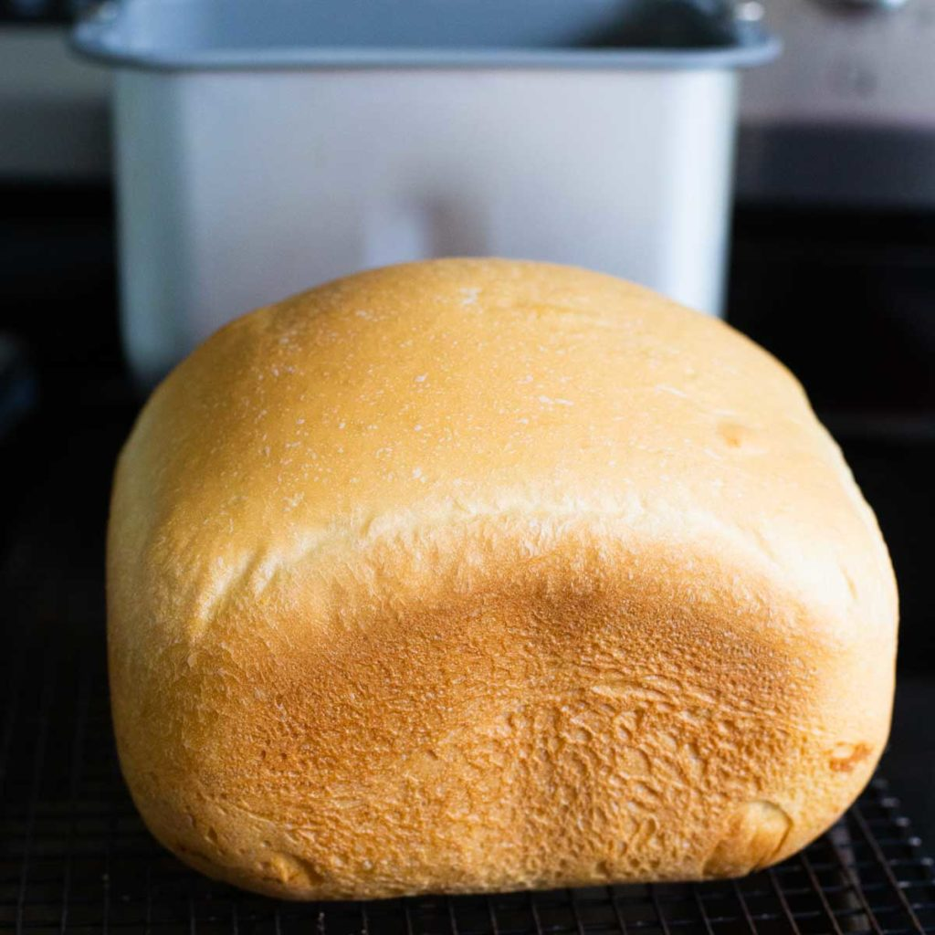 A loaf of bread machine bread cools on a wire rack with a bread pan in the background.