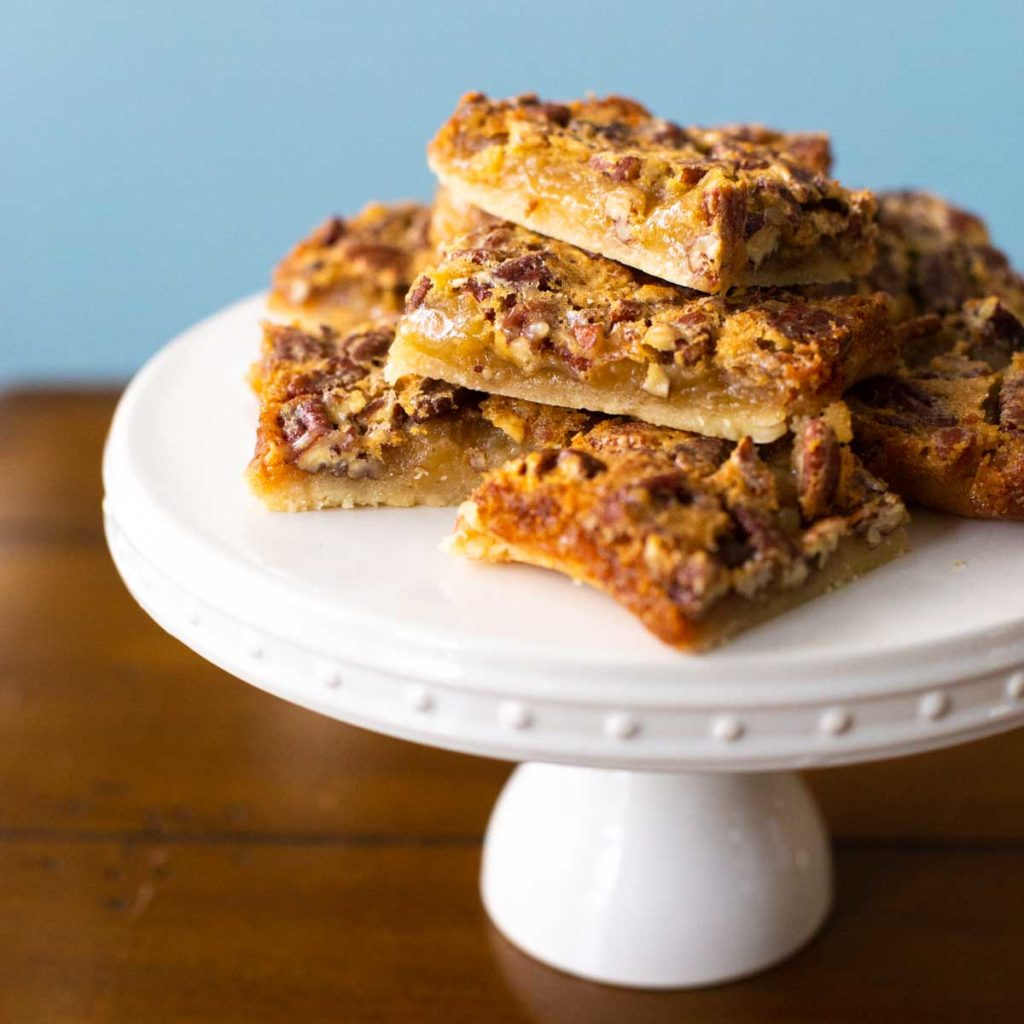 A stack of shortbread pecan pie bars on a cake plate for serving.