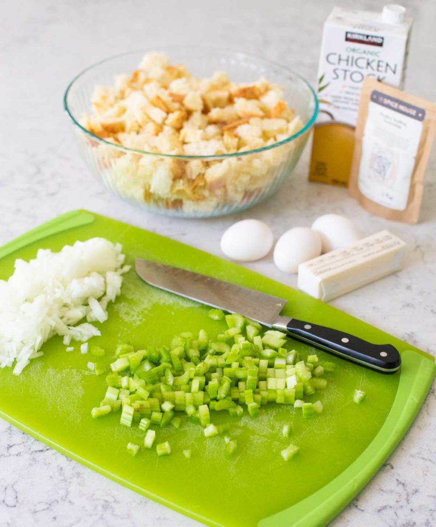 Prepped celery and onions are on a chopping board next to the rest of the stuffing ingredients.