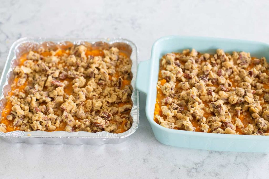 Two pans of sweet potato casserole have the pecan topping spread over the top.