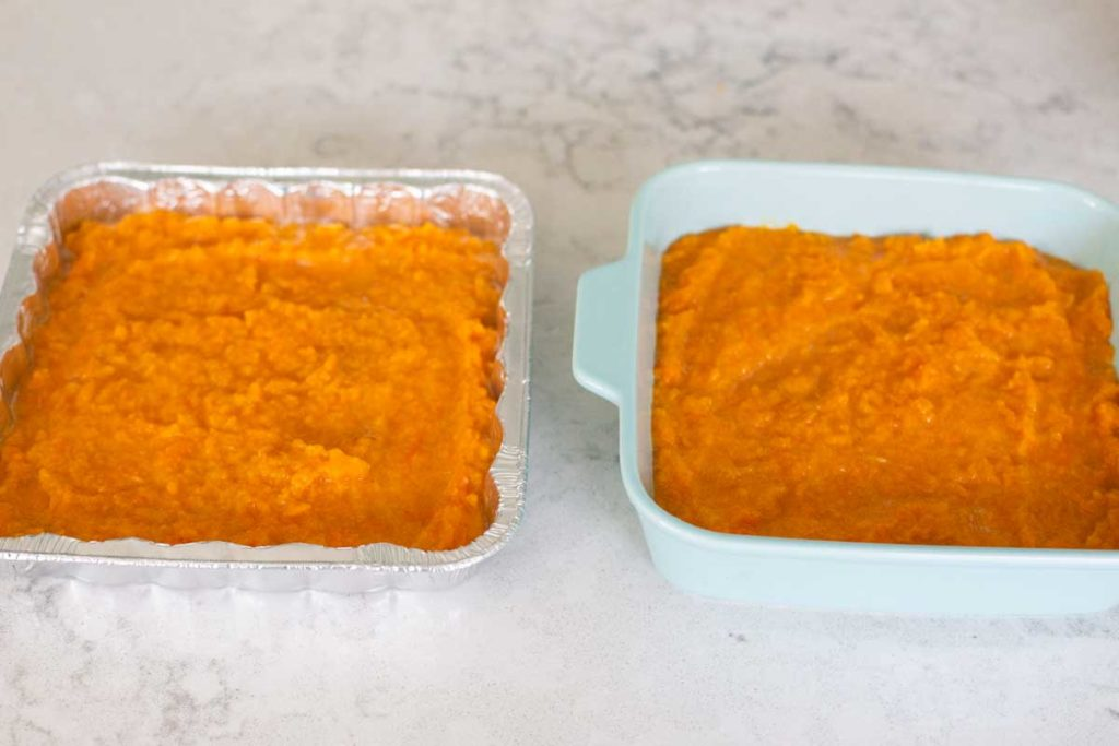 Two square pans have a layer of mashed sweet potato casserole filling spread evenly.