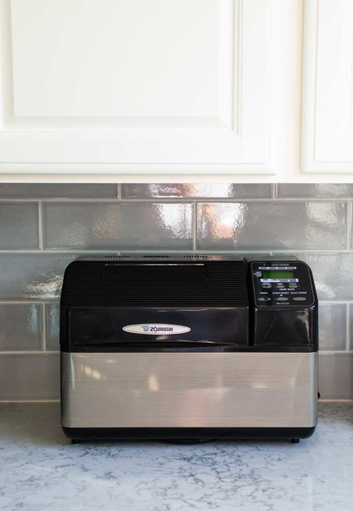 The Zojirushi bread machine sits on a kitchen counter underneath a kitchen cabinet.