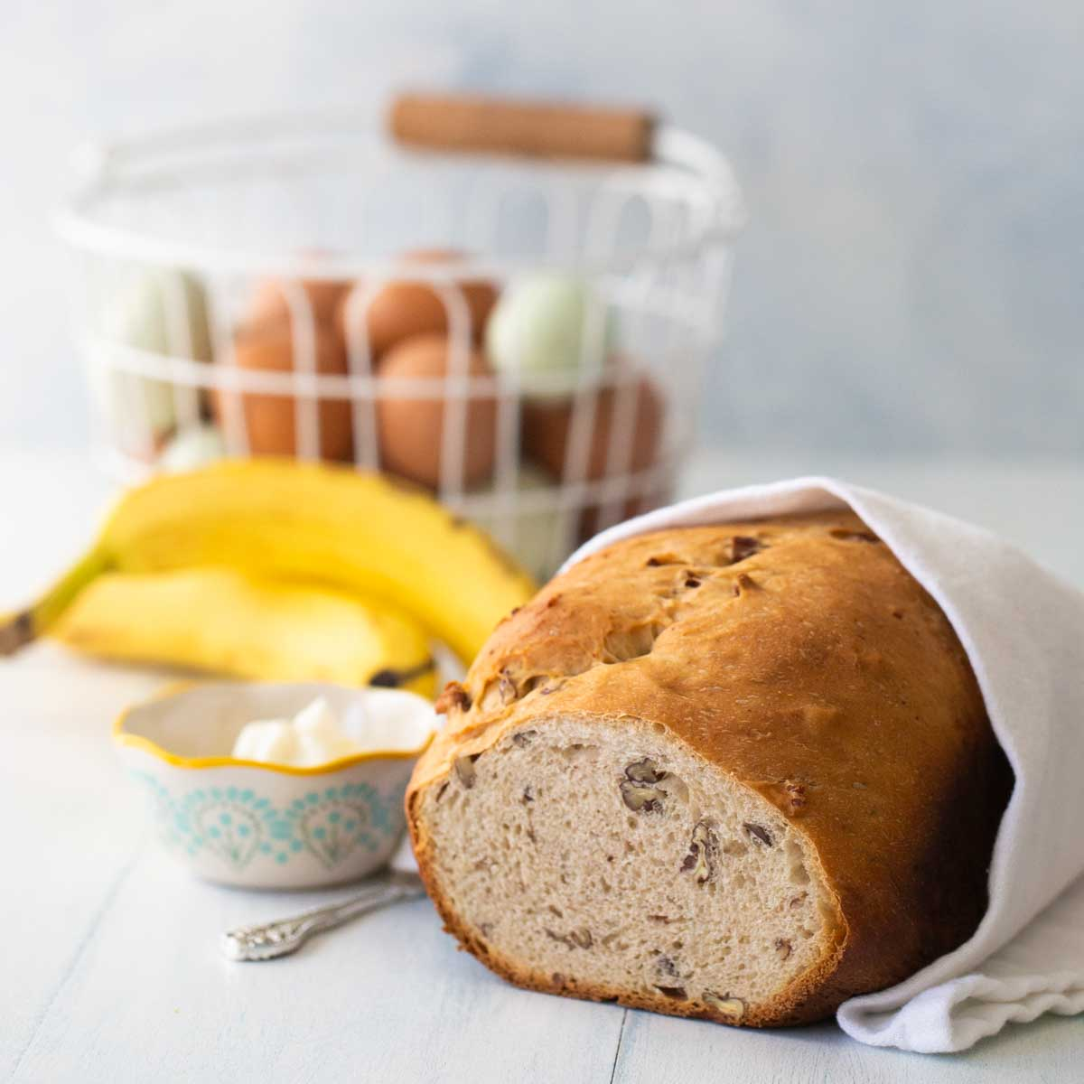 Banana bread wrapped in a tea towel sits next to fresh bananas and a bowl of cream cheese. A basket of eggs in the back.