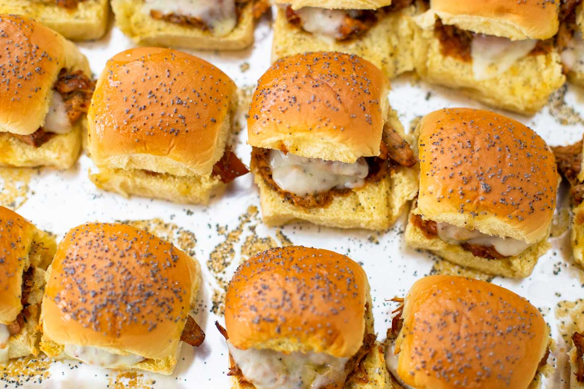 The finished baked BBQ chicken sliders are on a baking tray.