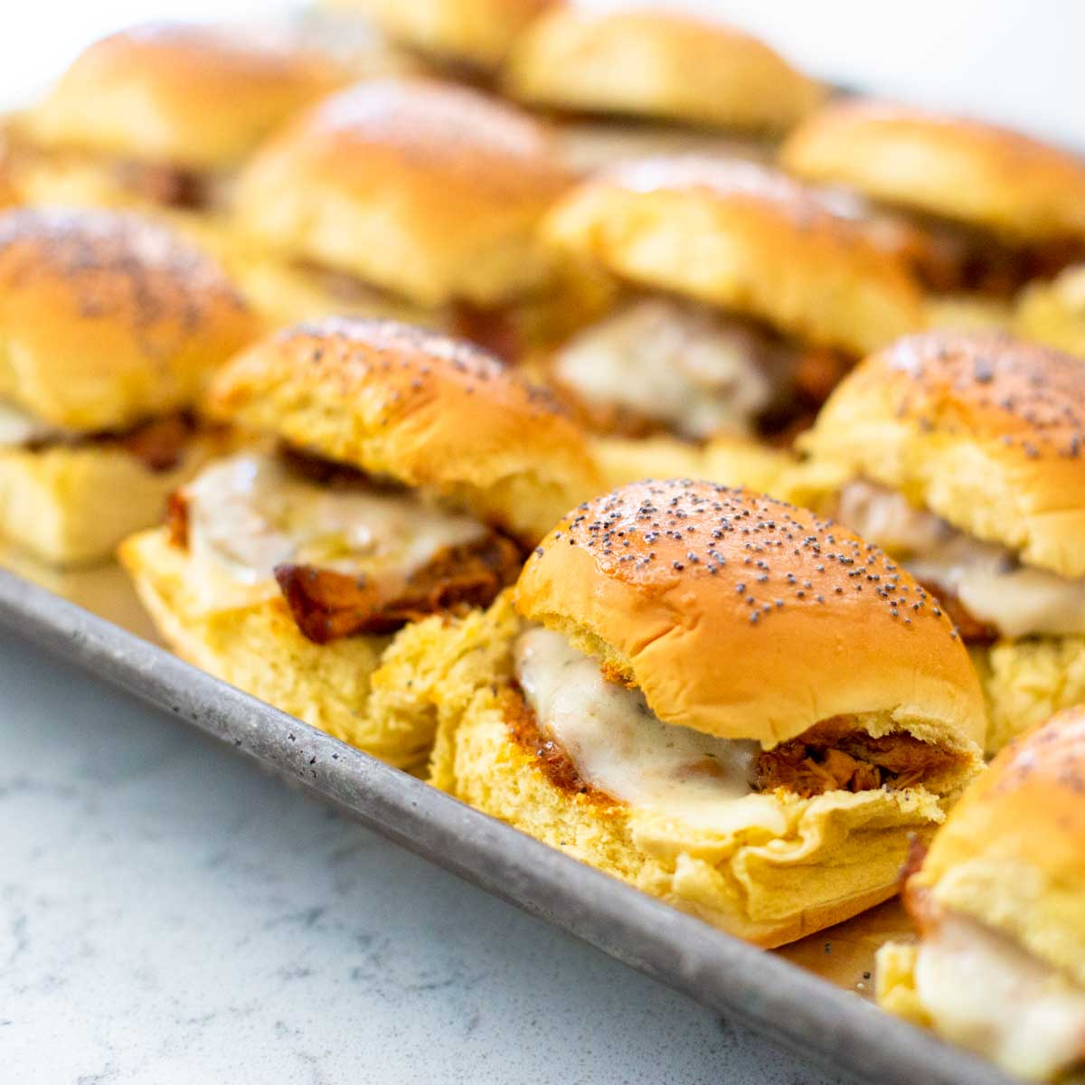 A metal baking pan has 3 rows of baked bbq chicken sliders showing the melted cheese oozing out.