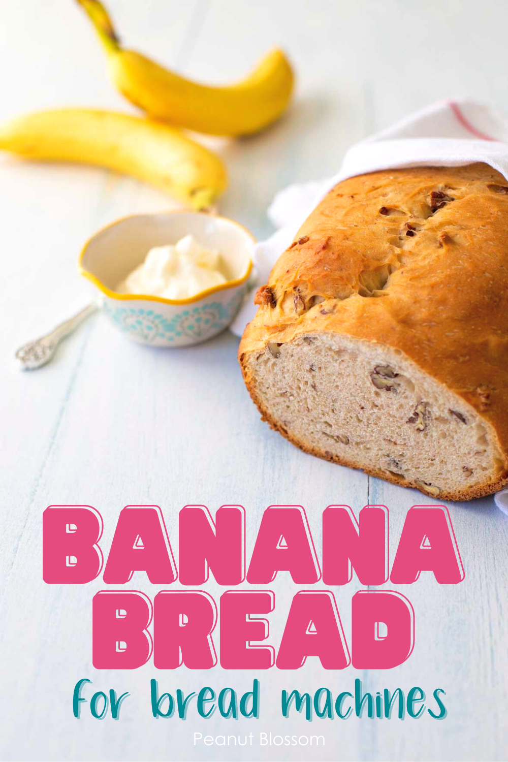 The finished banana bread sits on a table next to a few bananas and a bowl of cream cheese.