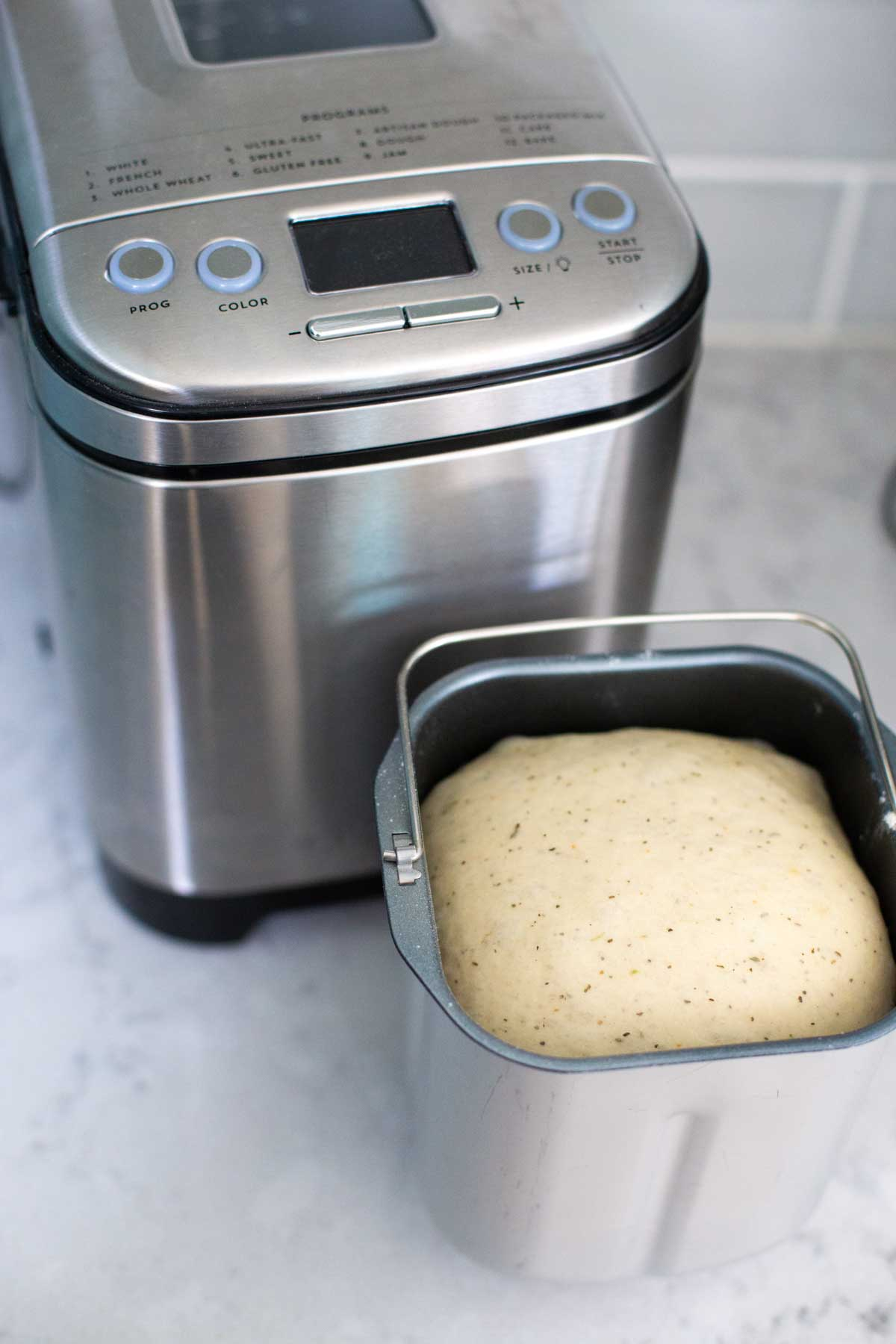 A bread pan filled with focaccia dough sits in front of a Cuisinart compact bread maker.
