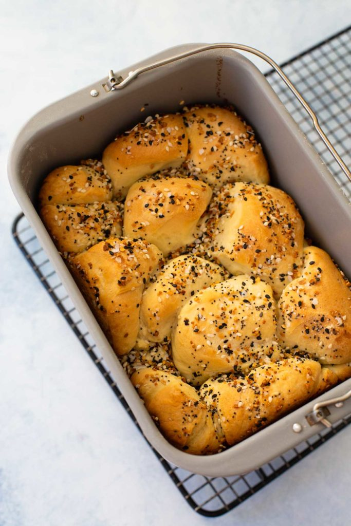 The baked Everything but the Bagel Bread sits in a bread machine bread pan on a wire rack.