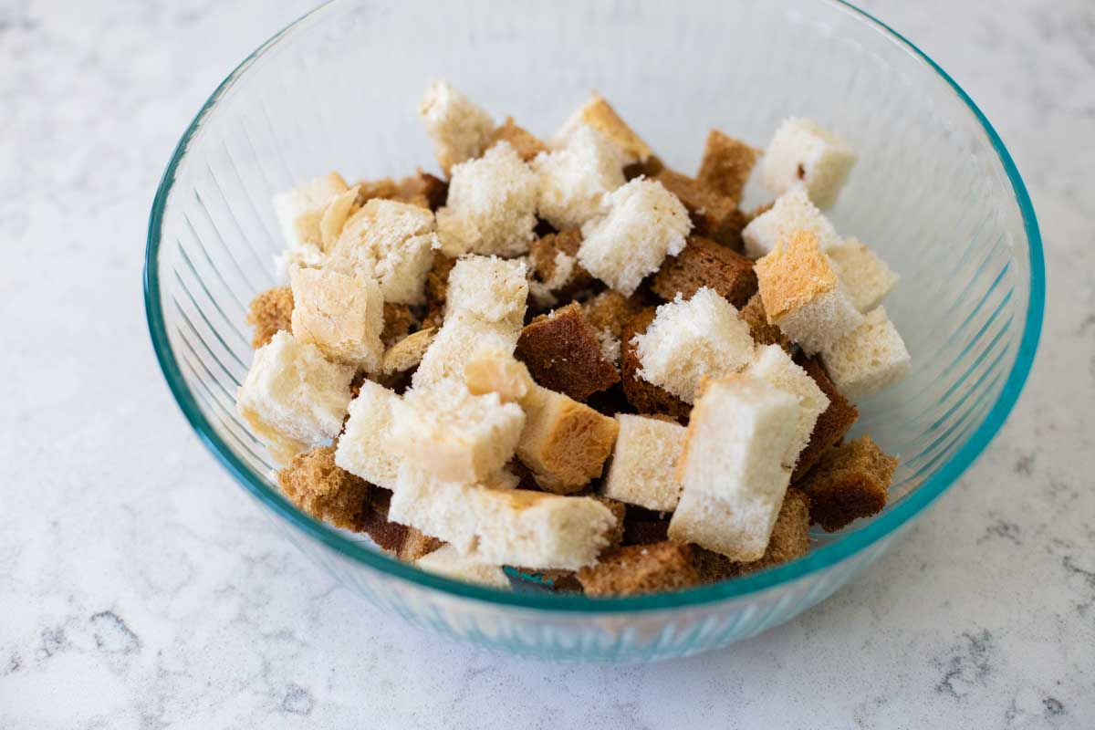 A mixing bowl shows a variety of bread being used to make croutons.
