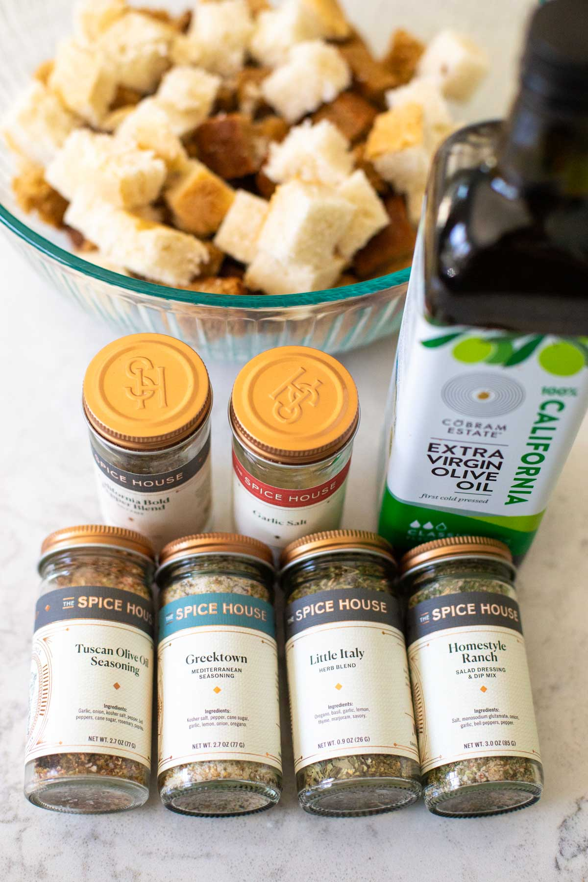 A variety of jars of seasonings that could be used to season the croutons sit next to a jar of olive oil.