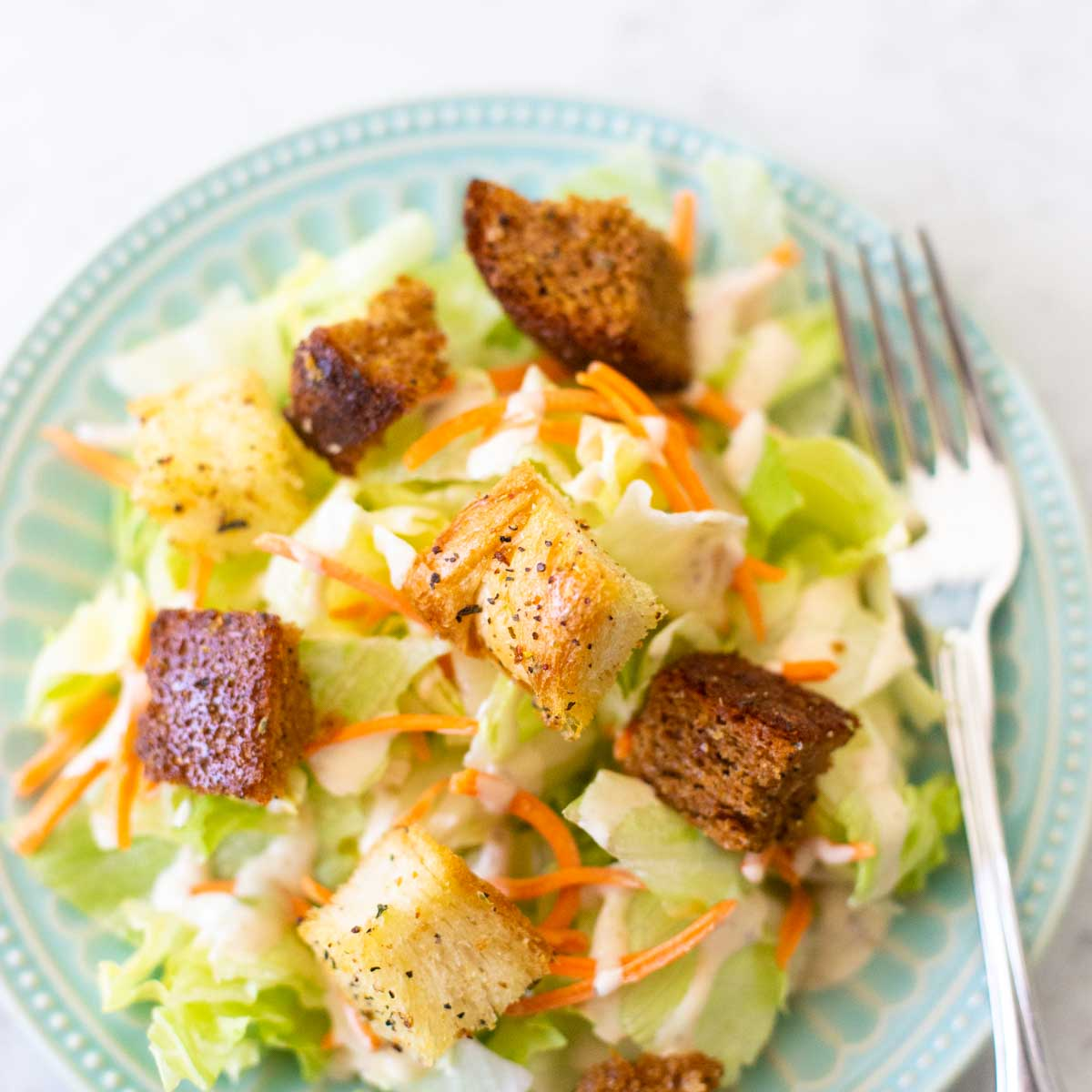 A simple green salad is topped with shredded croutons and homemade croutons made from bread machine bread.