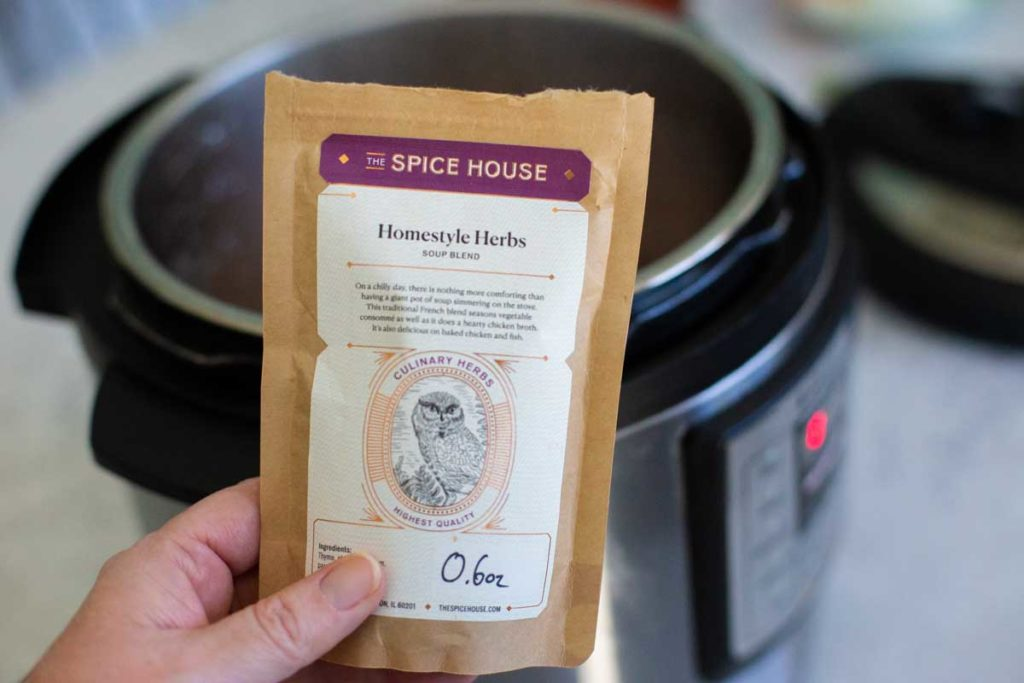 A hand is holding up the packet of soup herbs, an optional ingredient for the ground turkey soup.
