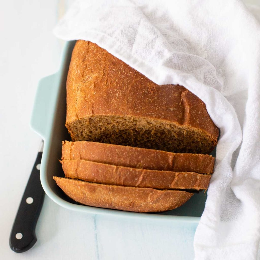 The steakhouse brown bread sits in a dish covered by a napkin with a knife on the side.