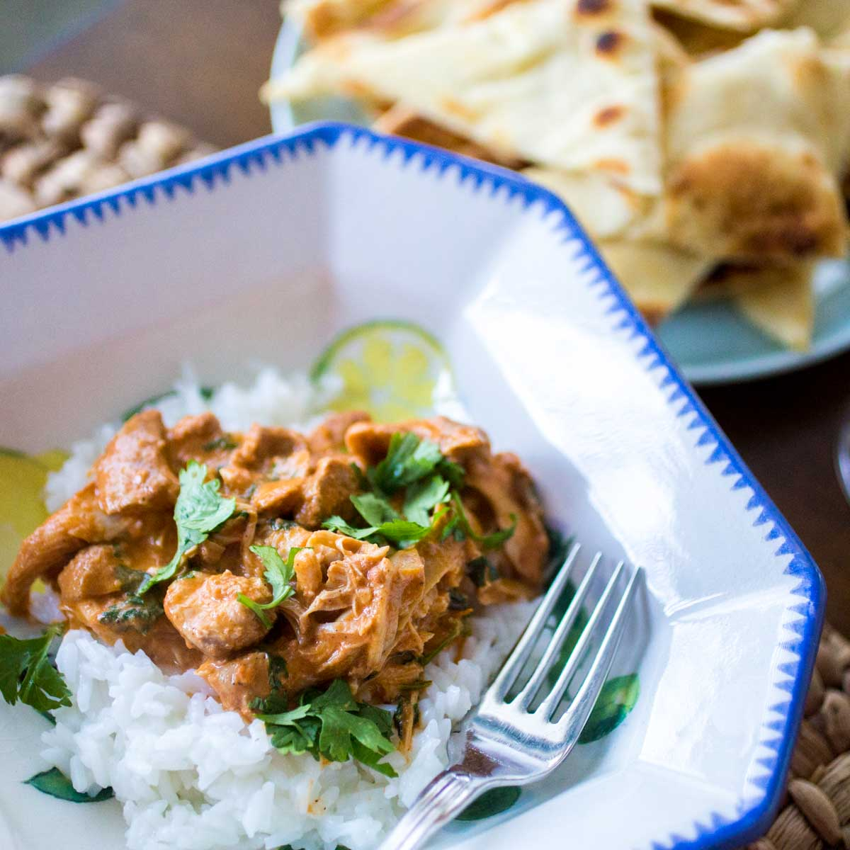 A dinner bowl has a serving of butter chicken spooned over jasmine rice. Fresh cilantro is sprinkled over the top.