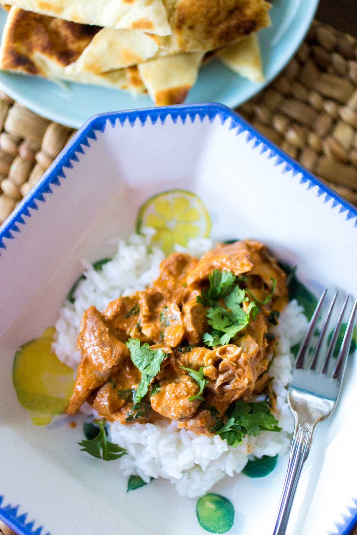 The final dish of butter chicken has been served in a dinner blow with rice and fresh cilantro.