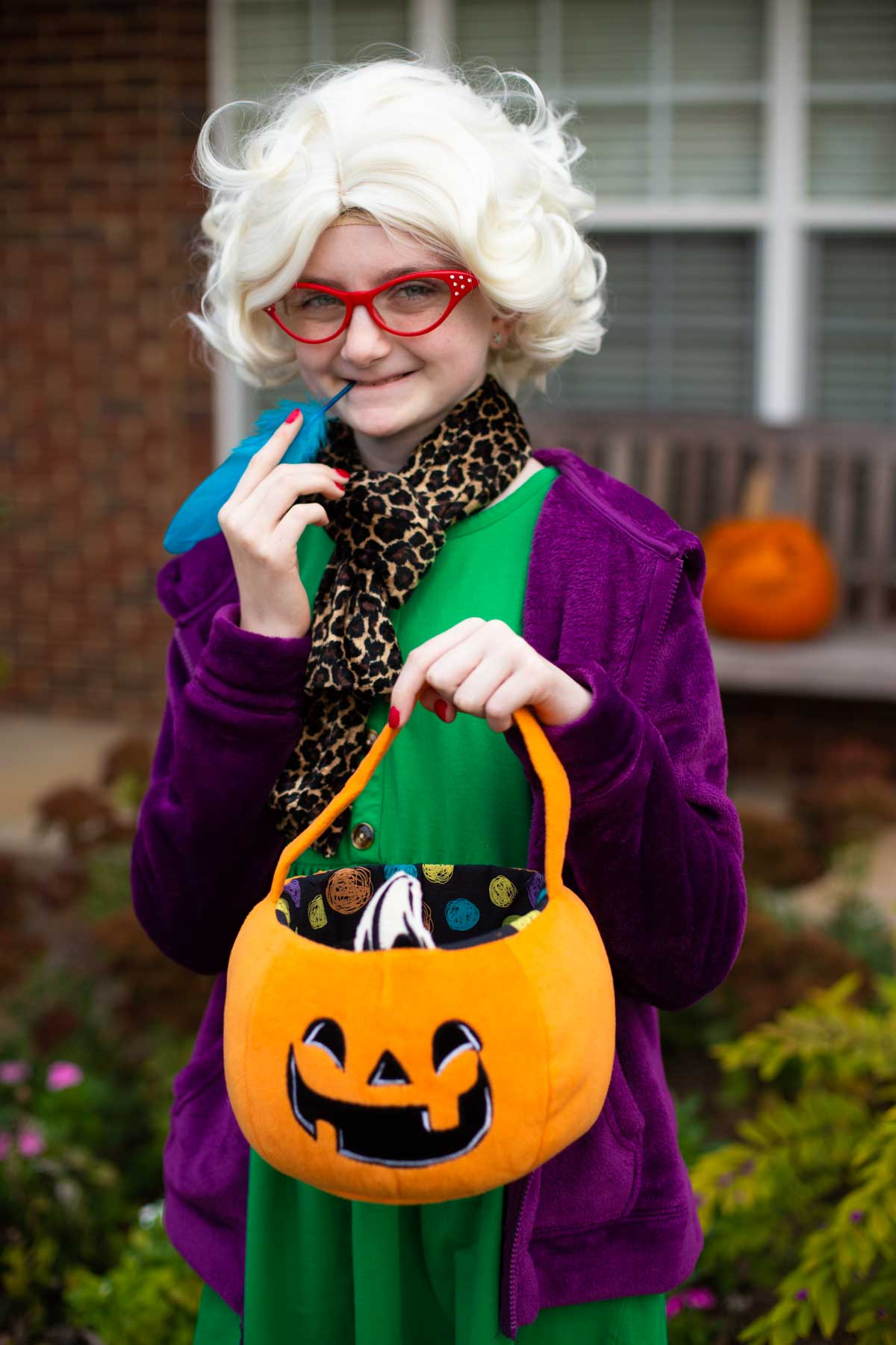 A young girl is wearing a Rita Skeeter wig, a green dress, a purple hoodie, and holding a pumpkin bag.
