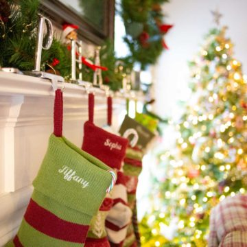 A row of stockings are hung on a mantle in front of a Christmas tree.