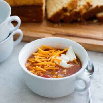A bowl of hot chicken taco soup has shredded cheddar and a dollop of sour cream on top. Sliced bread in the background.